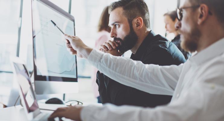 Mannen kijken naar statistieken op computer - Logistieke douane fiscale zaken - Jan Krediet
