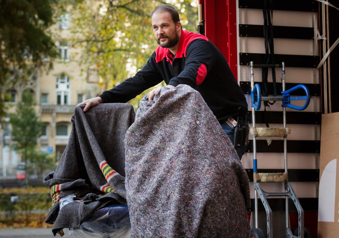Man laadt bureaustoelen uit vrachtwagen - Meubellogistieke oplossingen - Jan Krediet