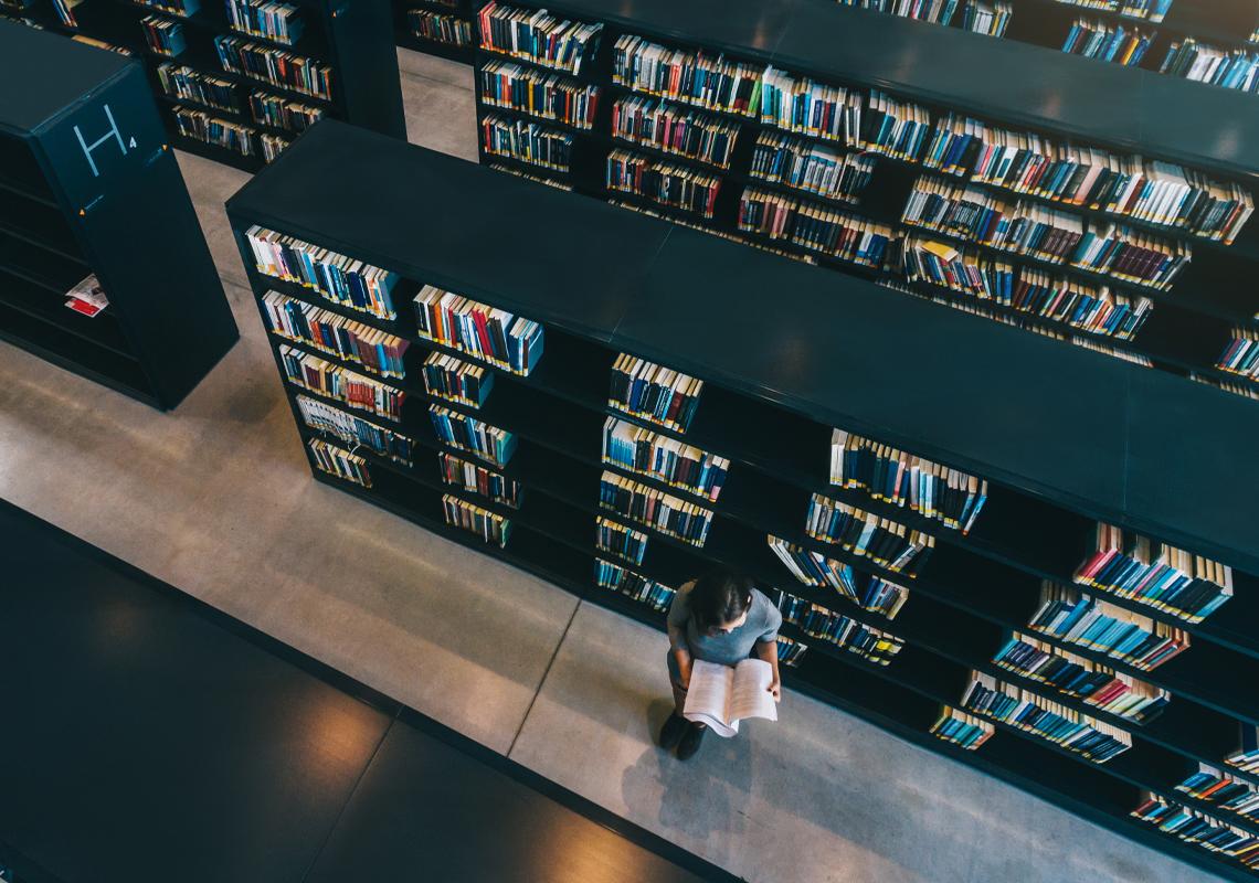 Vrouw leest boek in bibliotheek - Logistieke oplossingen publieke sector - Jan Krediet